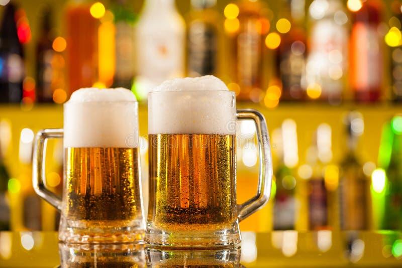 Brocche di birra servite sul contatore della barra immagine stock
