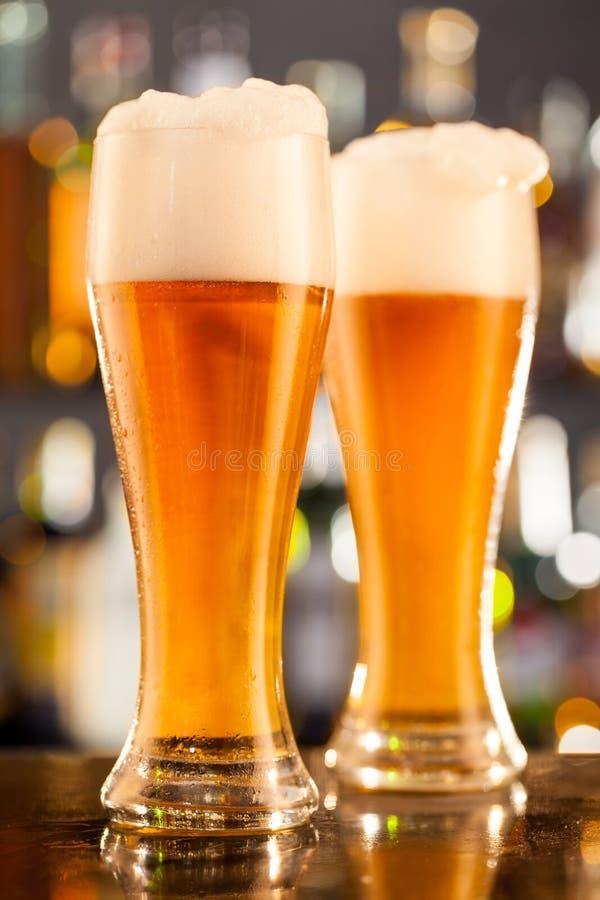 Brocche di birra servite sul contatore della barra immagini stock libere da diritti