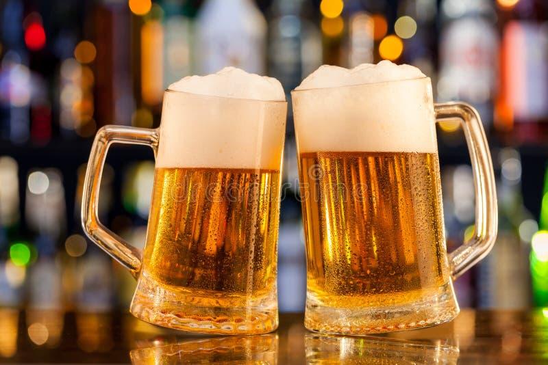Brocche di birra servite sul contatore della barra fotografie stock