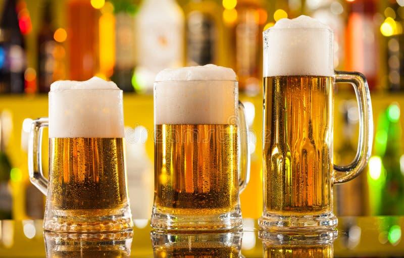 Brocche di birra servite sul contatore della barra fotografia stock libera da diritti