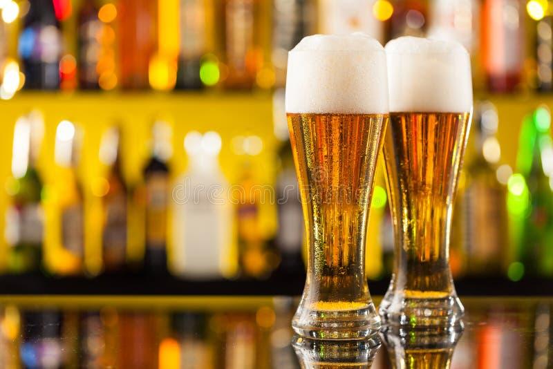 Brocche di birra servite sul contatore della barra immagini stock