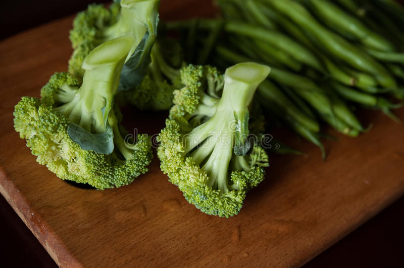 Broccoli and asparagus. Broccoli and green beans on a wooden board stock photography