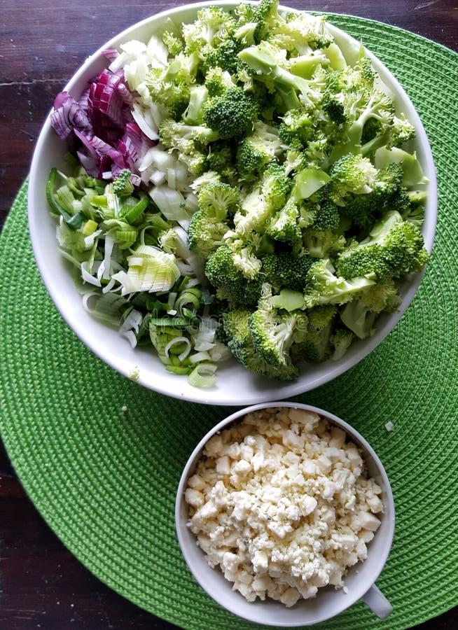 Broccoli, cipolle, porro tagliato in ciotole - ingredienti per il pasto vegetariano immagine stock