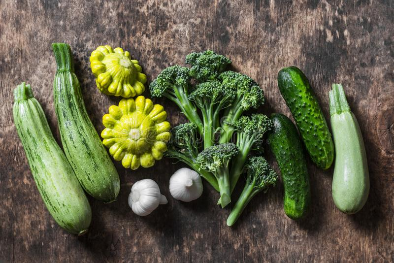Broccoli, courgette, pompoen, knoflook, komkommers - verse organische groenten op een houten achtergrond, hoogste mening Vlak leg stock fotografie