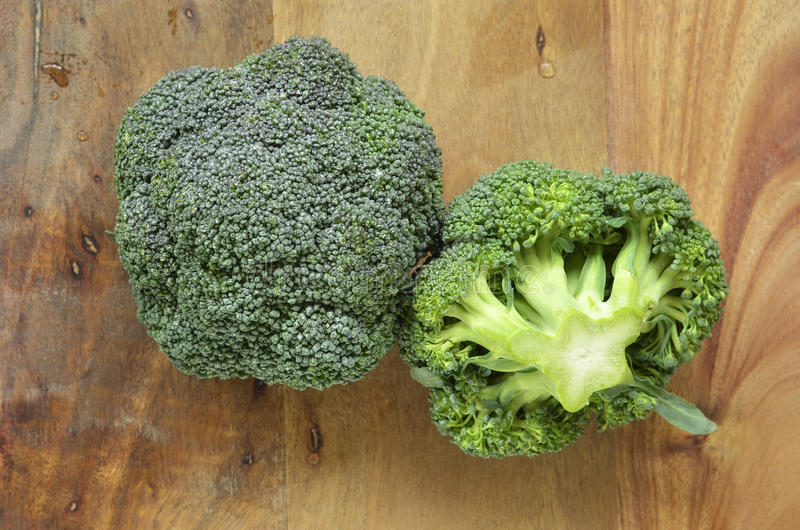 Broccoli crowns. Fresh washed broccoli crowns on rustic wooden cutting board stock photography