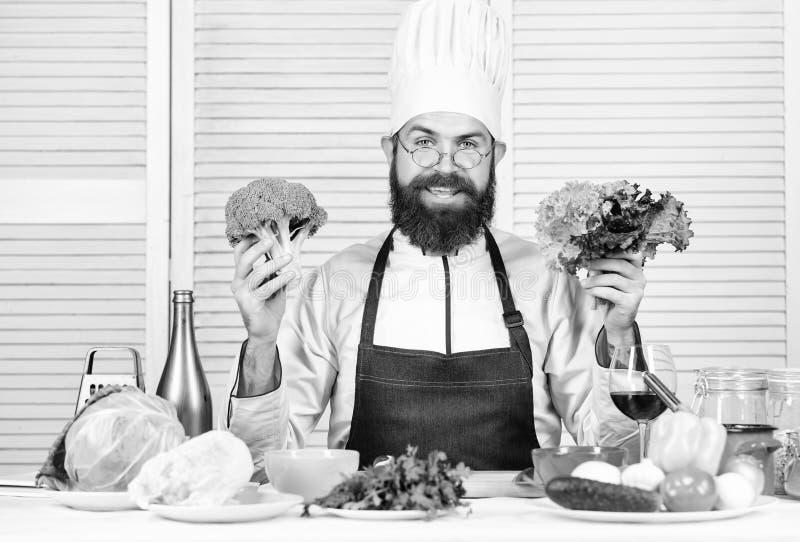 Broccoli della tenuta del cappello e del grembiule del cuoco dell'uomo Verdure organiche Concetto sano di nutrizione Cottura prof fotografia stock libera da diritti