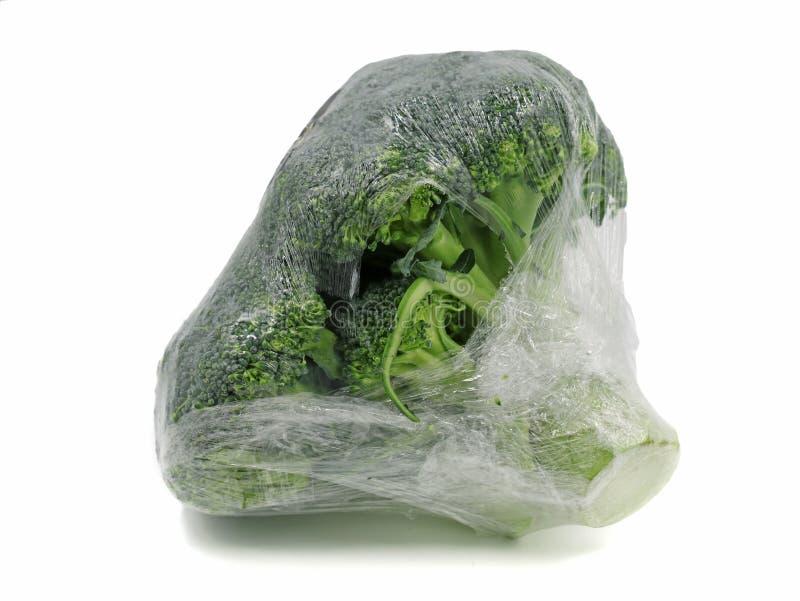 Broccoli die in plastic folie worden verpakt die op witte achtergrond wordt ge?soleerd stock afbeelding