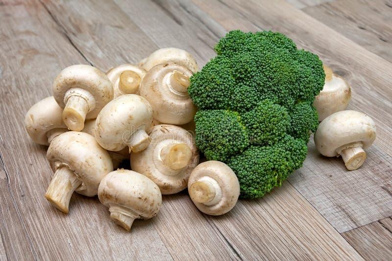 Broccoli e primo piano dei funghi prataioli dei funghi su un bordo di legno immagini stock libere da diritti