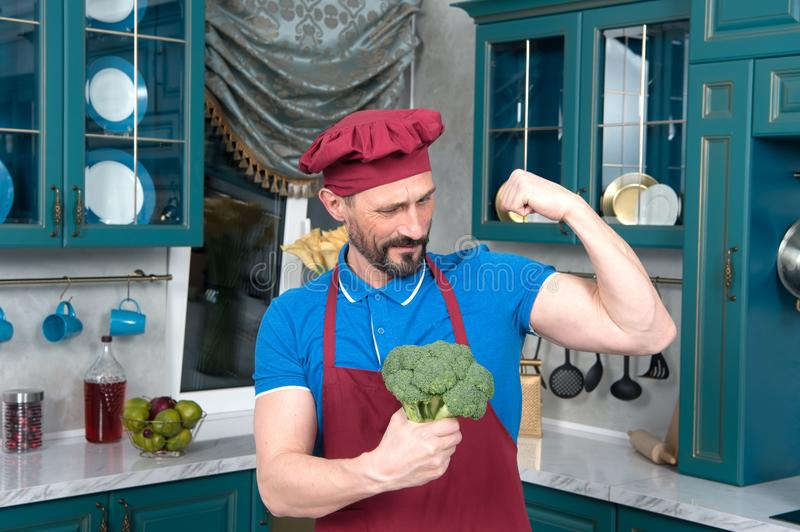Broccoli gives power to man. bicep or broccoli chose. Guy holds broccoli in hands and shows his bicep. royalty free stock images