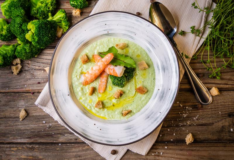 Broccoli green cream soup with shrimps in a plate on a rustic wooden background. Clean food, healthy diet concept. Top view, flat stock photo