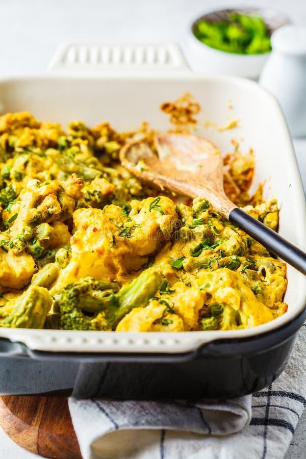 Broccoli, groene erwten en de braadpan van de bloemkoolkaas in de ovenschotel stock afbeeldingen