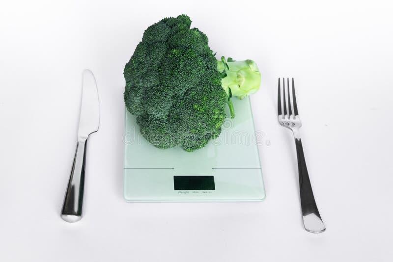 Broccoli på elektronisk kökvåg med kniven och gaffel på vit bakgrund äta för begrepp som är sunt royaltyfria foton