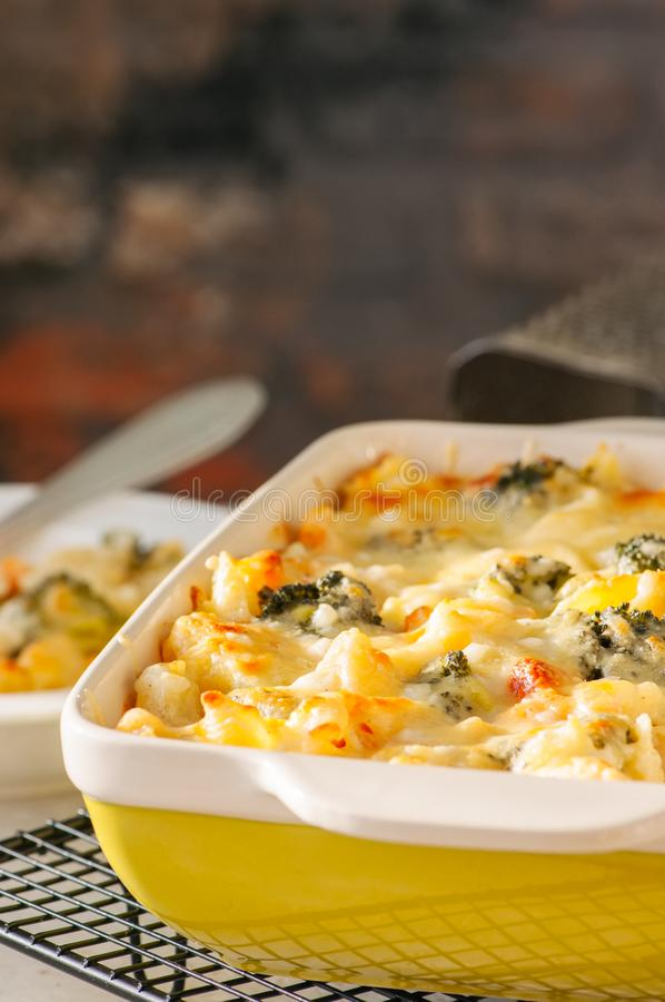 Broccoli and pumpkin mac and cheese in a ceramic dish on a wire stock image