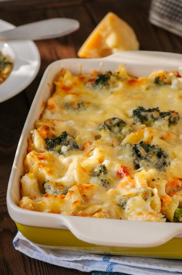 Broccoli and pumpkin mac and cheese in a ceramic dish on a wooden background. Close up. stock photos