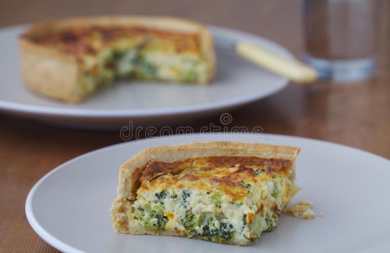 Broccoli Quiche. Slice on a plate with the whole quiche behind. Made with freerange eggs royalty free stock photo
