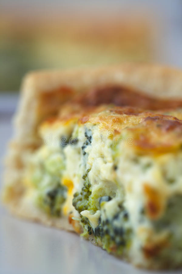 Broccoli Quiche Closeup. Closeup of Broccoli Quiche slice on a plate with the whole quiche behind. Made with freerange eggs stock images