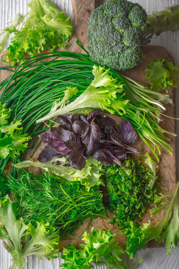 Broccoli, sla, basilicum, ui, dille op scherpe raad stock afbeeldingen