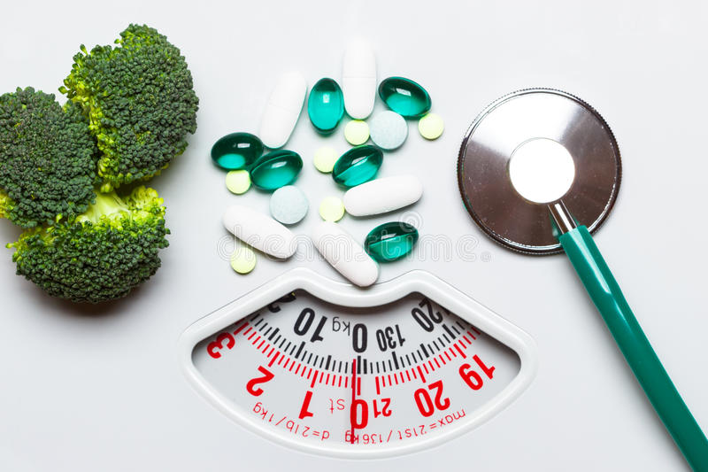 Broccoli stethoscope pills on weight scale. Dieting. Diet healthy eating weight control and health care concept. Closeup green broccoli stethoscope pills on royalty free stock image