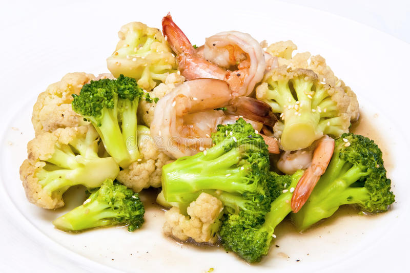 Broccoli stir-fried with cauliflower and shrimp. Decorated with white sesame royalty free stock photos