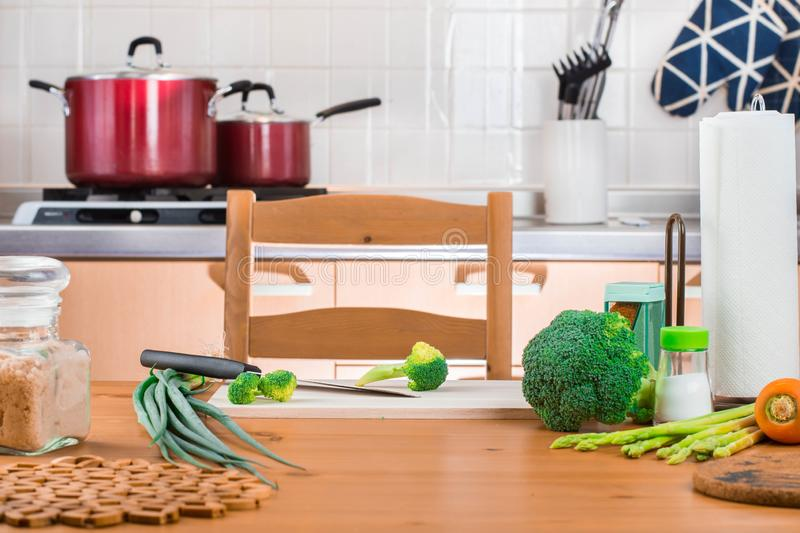Broccoli and vegetables on the table and cutting board with a knife in the kitchen ready to cook. royalty free stock photos