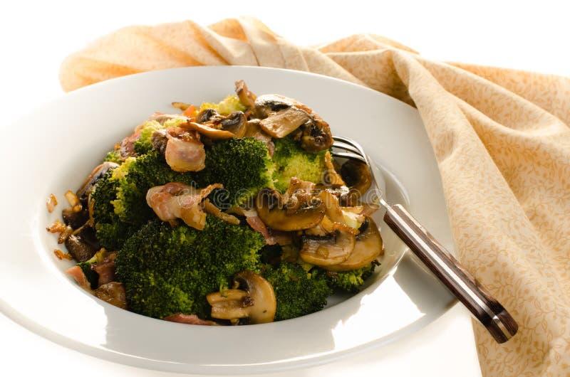 Broccolo saltato con bacon, la cipolla ed i funghi in zolla bianca fotografie stock libere da diritti