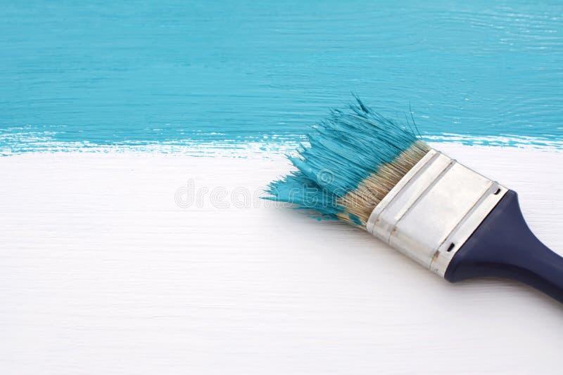 Brocha con la pintura azul, pintando sobre el tablero blanco foto de archivo