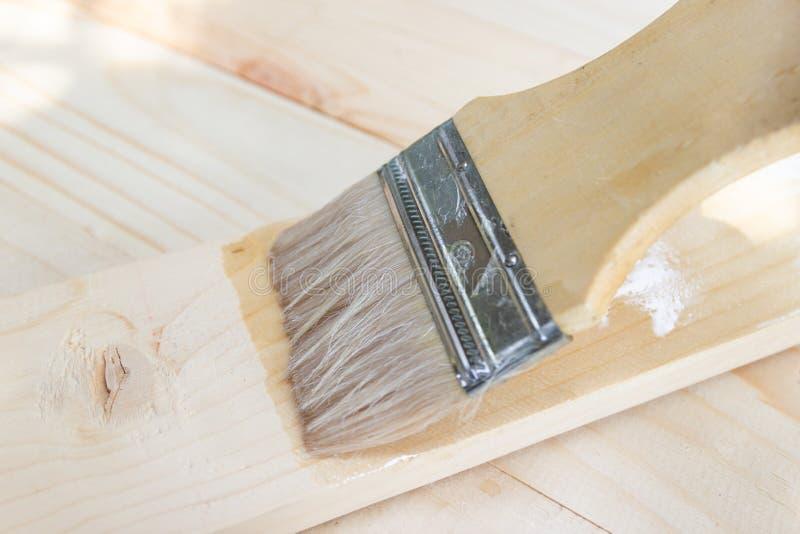 Brocha con la pintura de aceite de la laca en la madera fotografía de archivo