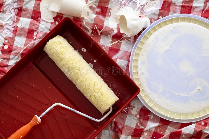 Brocha del rodillo en el envase del color con el color blanco en el re foto de archivo libre de regalías