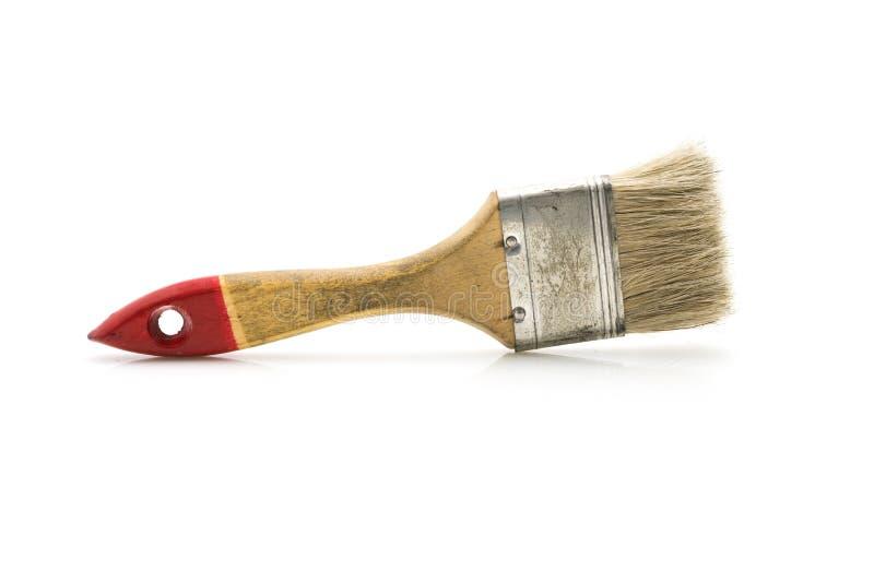 Brocha vieja y usada de la talla media, en el fondo blanco imagen de archivo libre de regalías