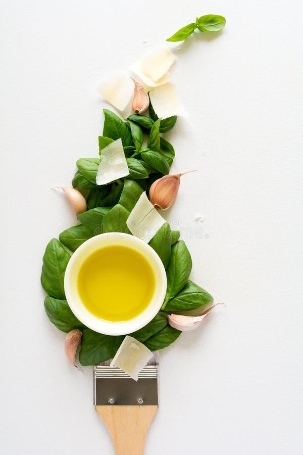 Brocha y lenguado de los ingredientes del pesto para cocinar la salsa: hojas de la albahaca, ajo, parmesano y aceite de oliva Con fotos de archivo libres de regalías