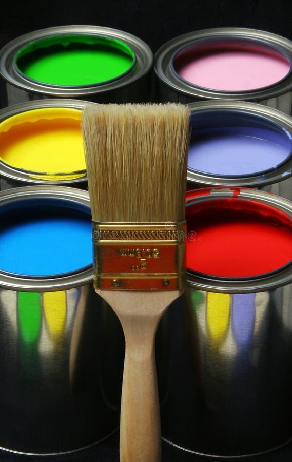 Brocha y pintura, latas de pinturas coloreadas primarias en el Ba negro fotografía de archivo libre de regalías
