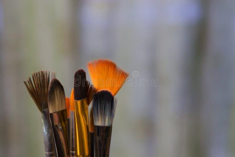 Brochas coloreadas artísticas con las cerdas blancas, negras y anaranjadas en un fondo borroso verde El lugar de trabajo del foto de archivo