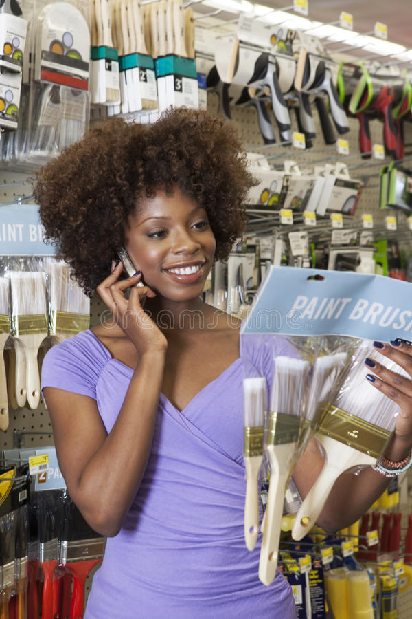 Brochas de compra de la mujer afroamericana en la ferretería fotos de archivo libres de regalías