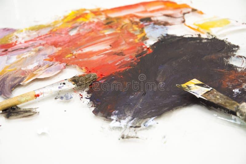 Brochas del artista en la paleta de madera pinturas de aceite mezcladas de la textura en diversos colores Herramientas de los ins imagen de archivo