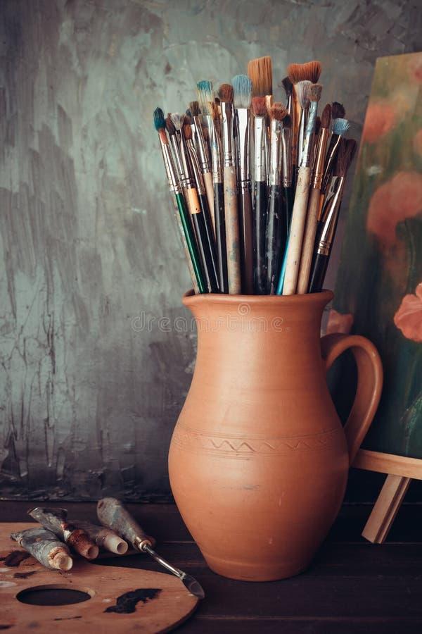 Brochas en jarro, paleta, tubos de la pintura y la pintura foto de archivo libre de regalías