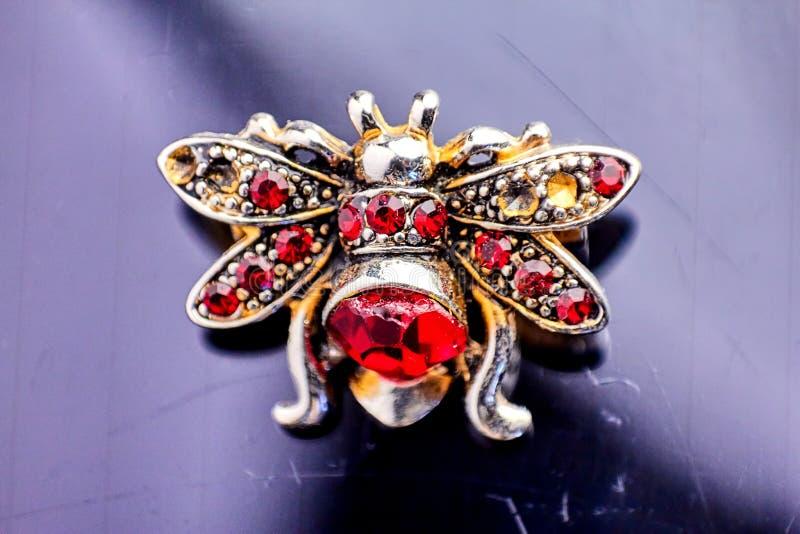 Broche de vintage sous forme d'abeilles faites de perles, tissu et cristaux, coupant sur un vieux fond noir photo libre de droits