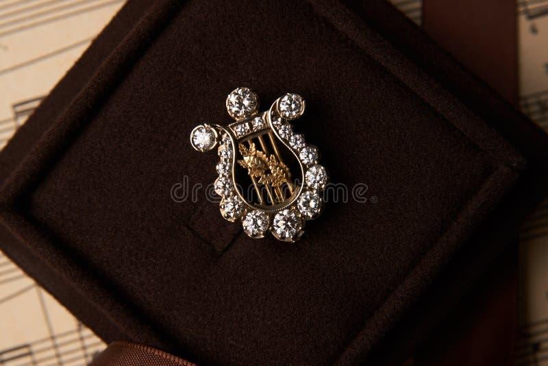 Broche del diamante bajo la forma de nota musical de una arpa en un regalo foto de archivo libre de regalías