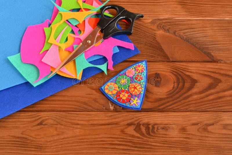 Broche hecha a mano del pedazo del fieltro, arte frugal Tijeras, pedazos del fieltro Fondo de madera con el espacio de la copia p imagen de archivo libre de regalías
