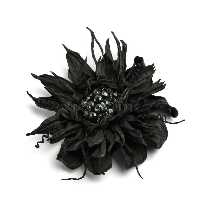 Broche original do artesanato feito do couro preto fino sob a forma de uma flor com as pedras pretas efervescentes no meio imagem de stock