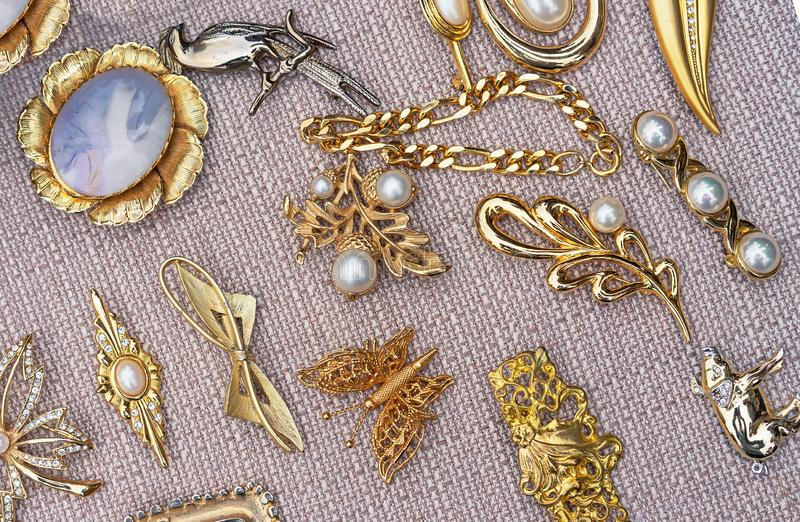 Broches avec des perles sur un fond beige Fond de bijoux pour la conception et la décoration images libres de droits