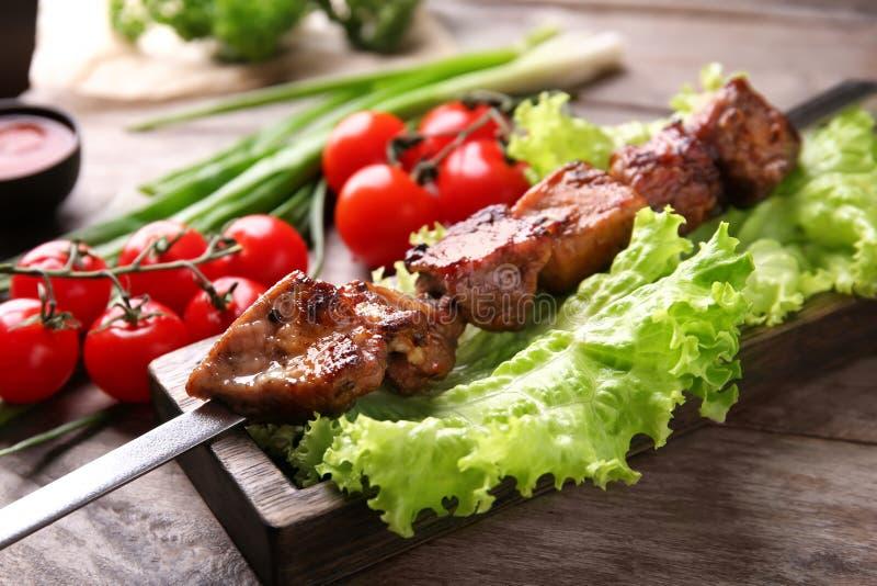 Brochette de barbecue avec de la viande et les légumes juteux sur la table en bois photo stock