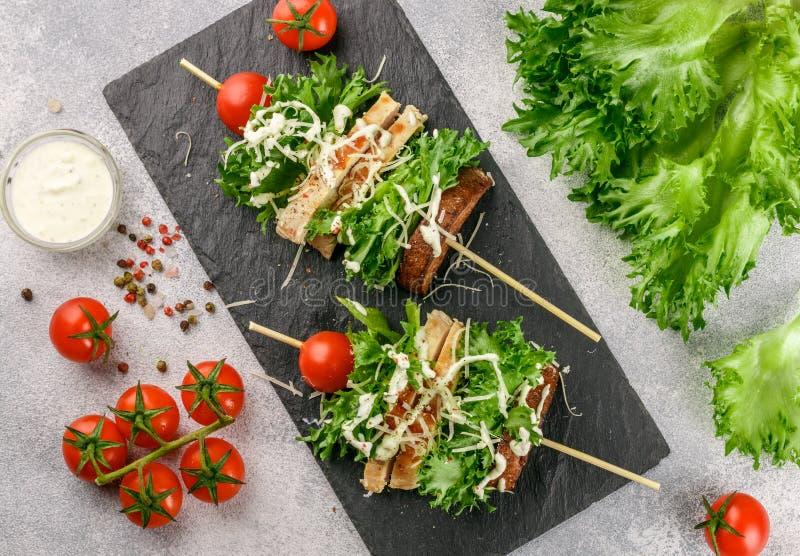 Brochettes délicieuses de laitue, de poulet, de tomate-cerise, de fromage et de sauce à César images libres de droits