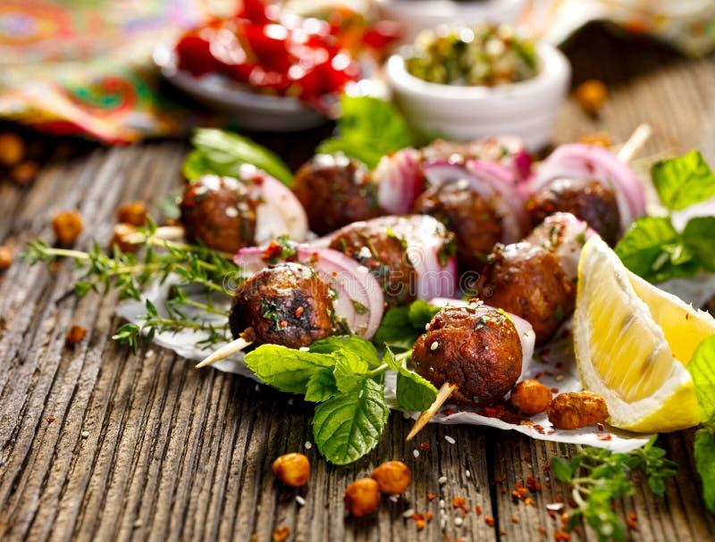 Brochettes de Kofta, boulettes de viande et oignon rouge avec l'addition de la menthe fraîche et du thym photographie stock libre de droits