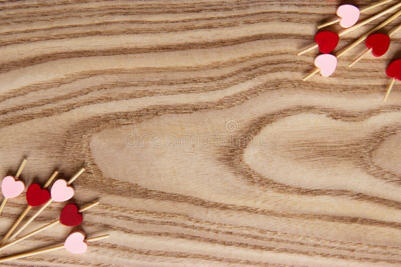 Brochettes en bois rouges et roses pour la nourriture avec un coeur Fond en bois pour le jour du ` s de St Valentine Configuratio photo libre de droits