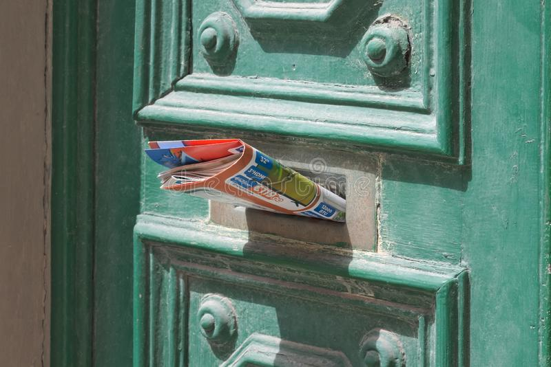 Brochure sticking out of front door letter slot mailbox. Tech brochure sticking out of front door letter slot mailbox royalty free stock photo