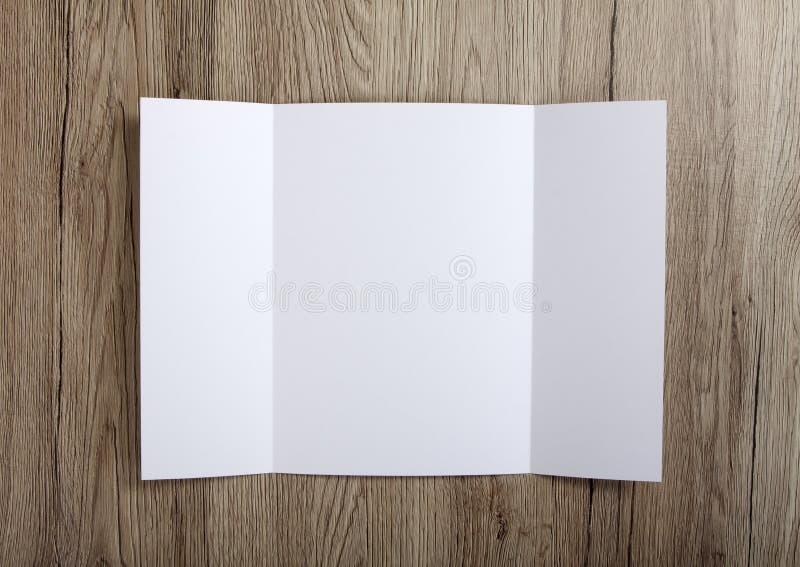 Brochure vide de pli de porte sur le fond en bois pour remplacer votre De image stock