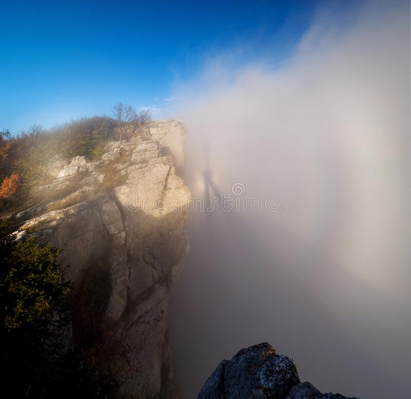 Brocken ghost at sunset in the Crimean mountains. Brocken ghost in the fog under the cliffs of the Crimean mountains in autumn stock photos