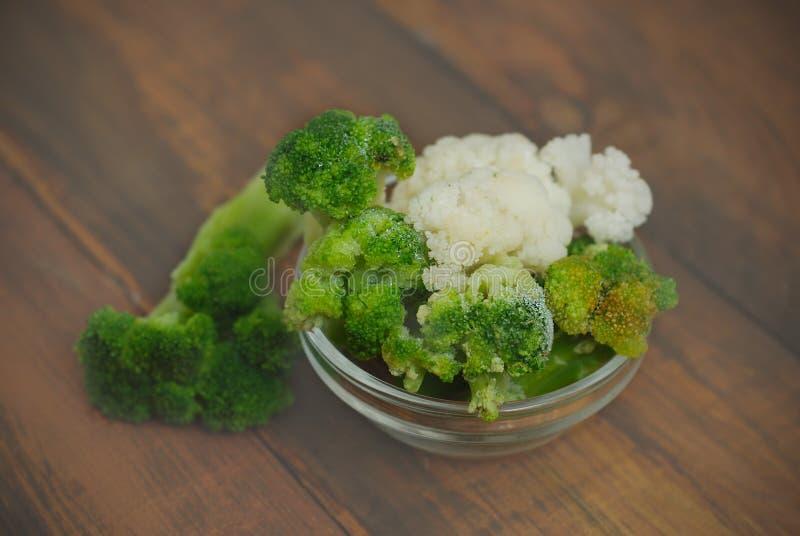 Brocoli和在土气木表的玻璃碗隔绝的花椰菜菜 顶面vieaw 饮食和健康食物 库存图片
