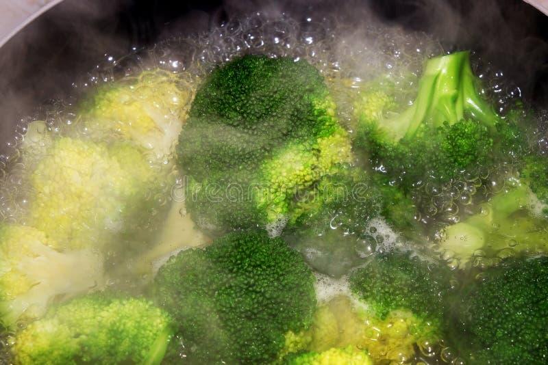 Brocoli faisant cuire en eau bouillante dans la casserole sur une fraise-mère images stock