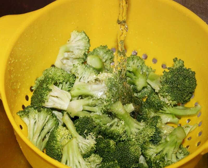 Brocoli organique de coupe fraîche dans la passoire jaune étant rincée sous l'eau image libre de droits
